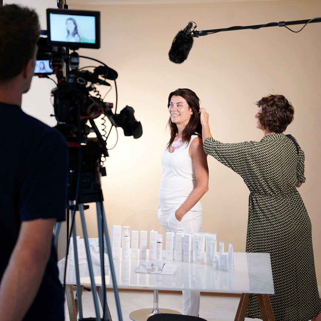 Nicola Tiggeler wird von der Stylistin zurecht gemacht. Im Vordergrund sind die Kamera und das Mikrofon zu sehen.