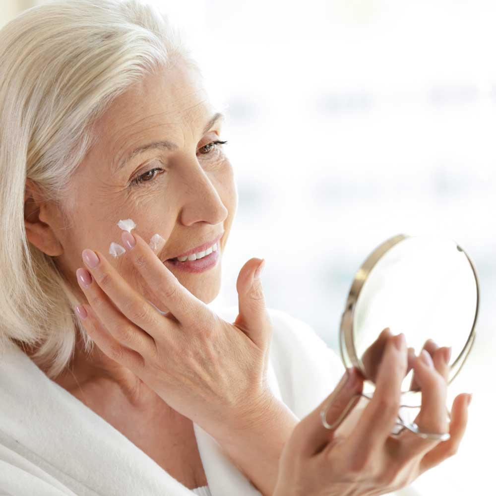 Ältere Frau mit einem Kosmetikspiegel in der Hand cremt sich das Gesicht ein