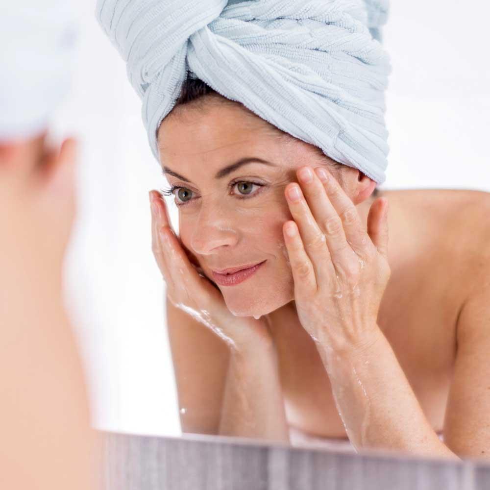 Frau mit Turban auf dem Kopf wäscht sich das Gesicht, um es für die Pflege vorzubereiten
