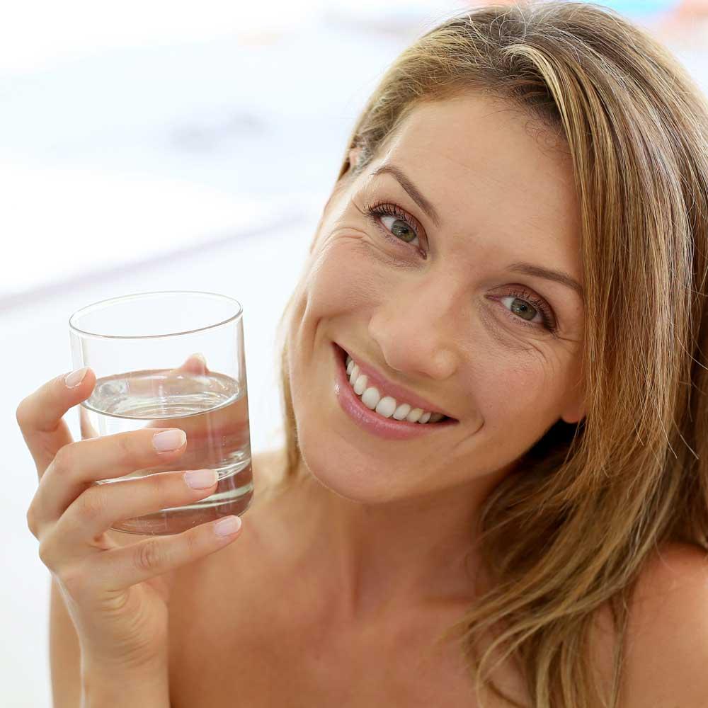 Frau mit gefülltem Wasserglas lächelt in die Kamera