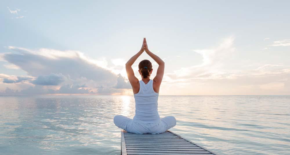 Frau sitzt im Yoga-Sitz mit Blick aufs Meer entspannt auf einem Steg