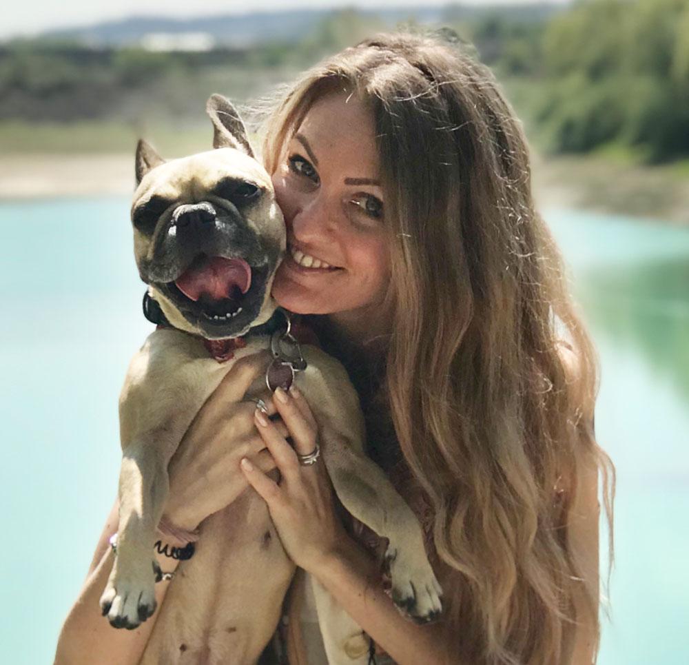 Marina hält lächelnd ihren Hund auf dem Arm. Der Hund zeigt seine Zunge.