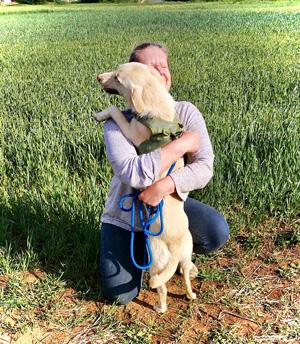 Astrid umarmt kniend einen blonden Hund. Die beiden befinden sich draußen im Grünen.