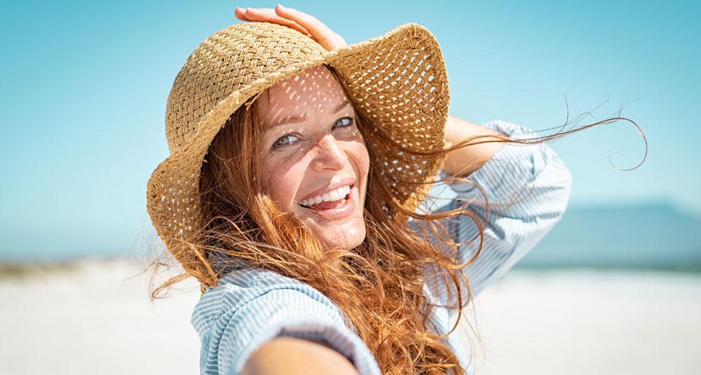 Frau lächelt in die Kamera. Sie hat Spaß am Strand, trägt als Schutz vor Hautalterung Sonnenhut und Kleidung.