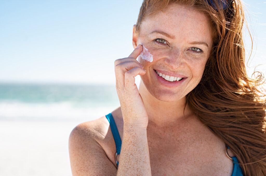 Fröhliche Frau mit Sommersprossen cremt sich am Strand mit Sonnencreme ein.